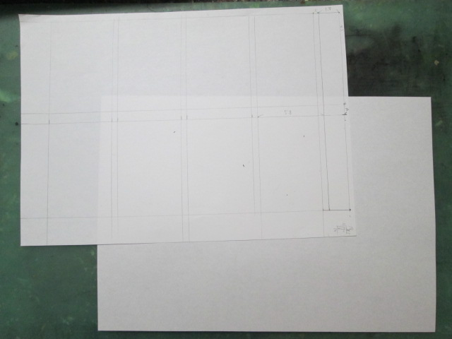 四コマ漫画の枠線の型に紙を重ねようとしている画像