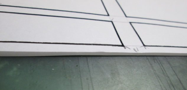 四コマ漫画の枠線の型に紙を重ねている画像