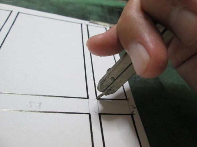 四コマ漫画の枠線の角をすべてコンパスの針で穴をあけている画像