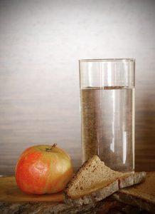 コップとりんご、パンがある画像